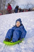 picture of snow-slide  - young boy on sledge sliding down on snow - JPG