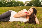 stock photo of eat grass  - Stunning young brunette eating apple lying on grass in sunshine - JPG