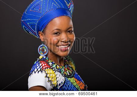 smiling zulu woman in traditional clothes looking at the camera on black background