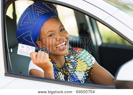 happy african woman showing her driver's license she just got