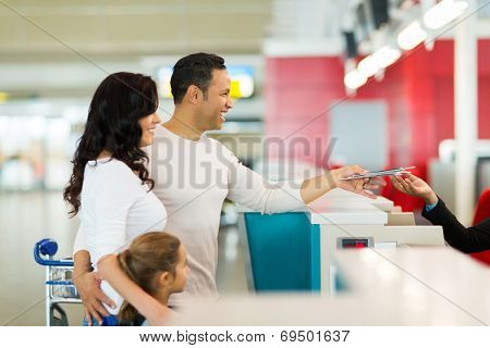 cheerful family handing over air ticket at airport at check in counter