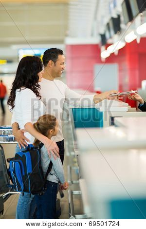 family checking in at airline counter in airport