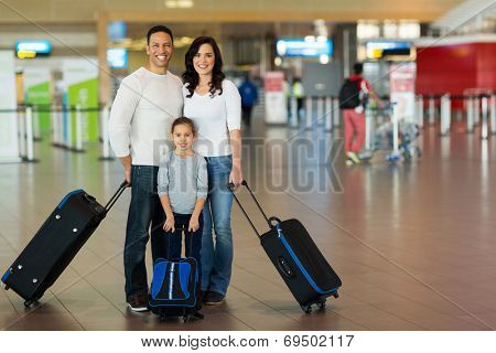 happy family with suitcases at airport