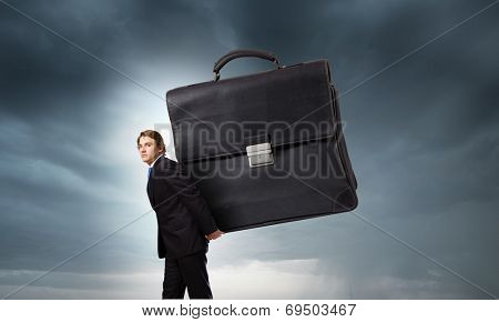 Young determined businessman carrying big heavy suitcase