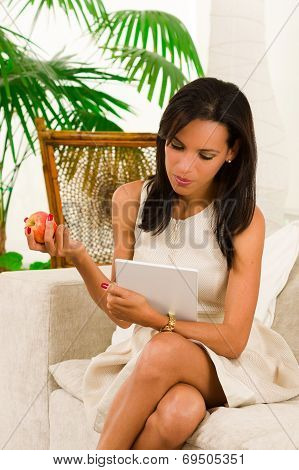 Beautiful young elegant woman sitting in livingroom using digital tablet and eating an apple