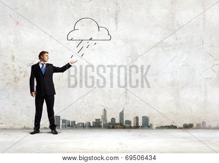 Young businessman catching raindrops with palm. Failure concept