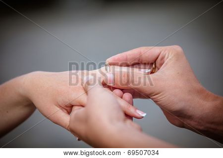 Man placing a diamond engagement ring on the finger of his fiance. Shallow depth of field with focus on the ring