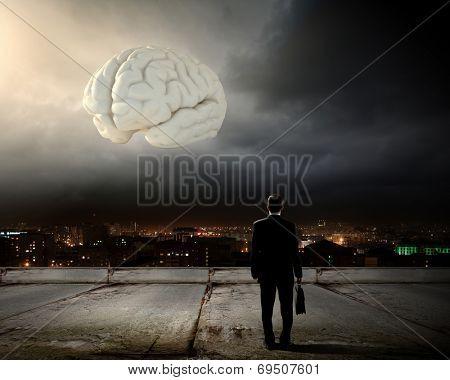 Rear view of businessman looking at big brain model