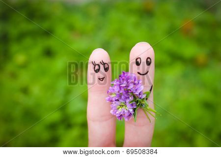 Happy couple. Man is giving flowers to a woman.