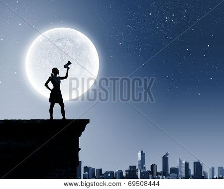 Silhouette of woman on top of building and screaming in megaphone