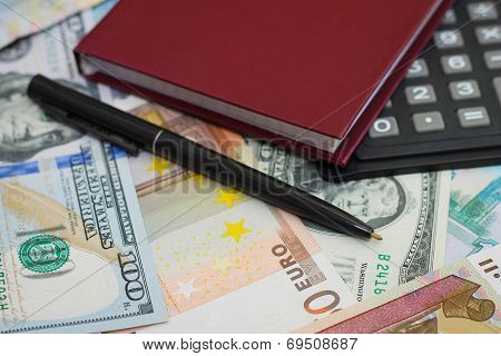 Calculator, pen and Notepad on the background of money