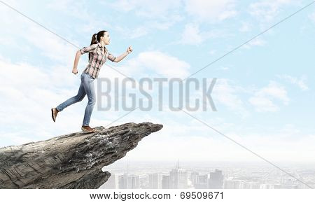 Young woman in casual running on edge of rock