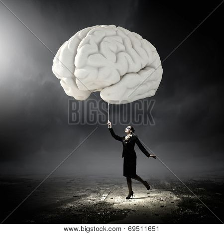 Huge human brain and young businesswoman in glasses