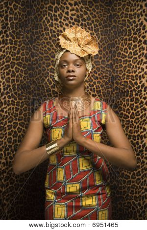 Young African American Woman Praying And Wearing Traditional African Dress