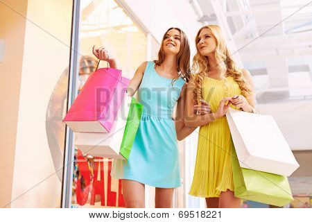 Portrait of happy girls in smart casual with paperbags discussing clothes in shop window