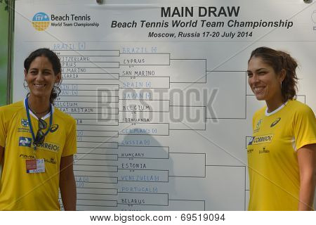 MOSCOW, RUSSIA - JULY 17, 2014: Joana Corez and Samantha Barijan of Brazil against draw board on the Beach Tennis World Team Championship. Girls share No 1 in the world rankings