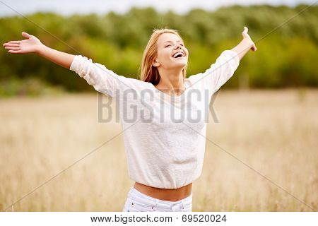 Image of happy woman with outstretched arms standing in field