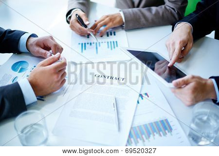 Image of business documents, touchpad, pen and glasses on workplace at meeting