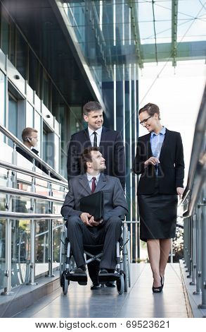 Businessman On Wheelchair And His Co-workers