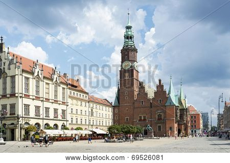 POLAND, WROCLAW - AUGUST 3: Tourists visit the Old Market Square and gothic Town Hall on 3 August 2014 in Wroclaw, Poland.