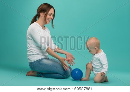 Young Caucasian attractive smiling mother playing with cute baby