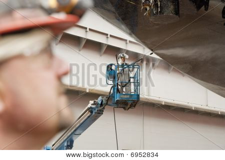 Worker In Man Lift Cleaning Ship Hull
