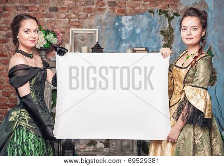 Two Beautiful Women In Medieval Dresses With Empty Paper