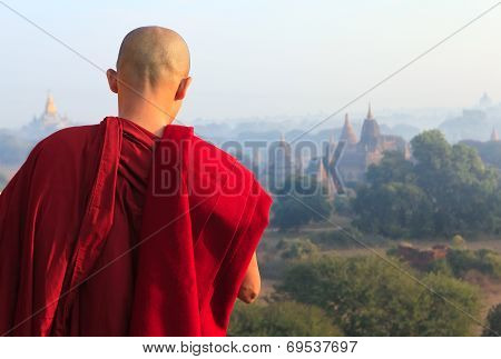 A monk standing in front of vast of temples valley in ancient Bagan city, Mandalay region, Myanmar.