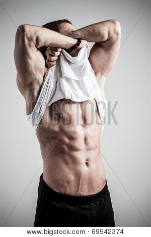 Brutal athletic man taking shirt off on gray background