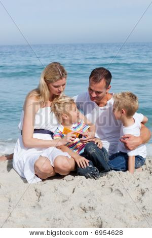 Caring Mother With Her Family Holding Sunscreen