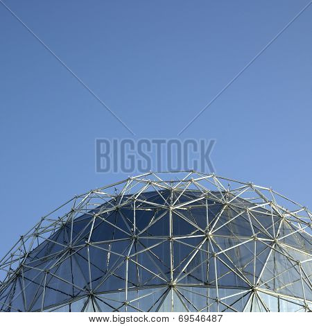 Large silver geodesic dome and blue sky