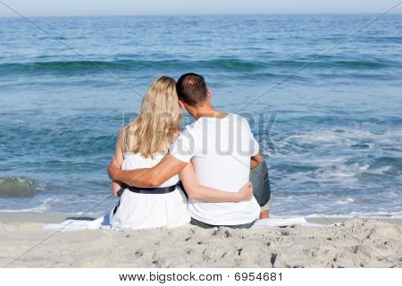 Affectionate Couple Sitting On The Sand At The Beach