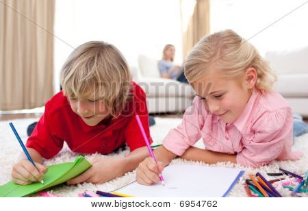 Adorable Siblings Drawing Lying On The Floor
