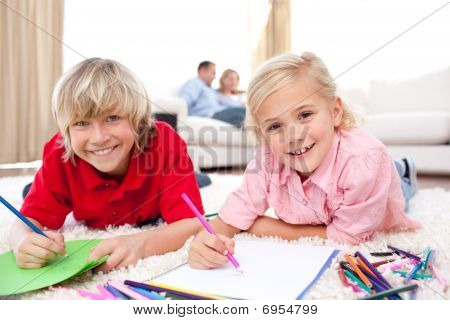 Lively Siblings Drawing Lying On The Floor