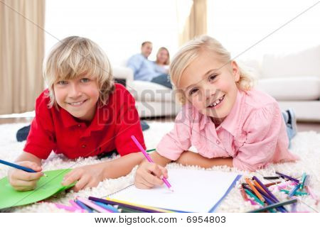 Happy Siblings Drawing Lying On The Floor