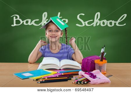 Happy little girl in the school bench behind Back To School sign on the blackboard