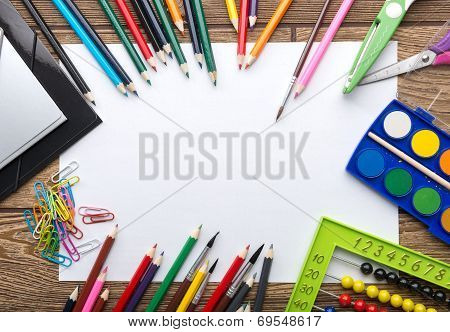 School stationery frame on wooden background: paper pencil brush scissors folders abacus