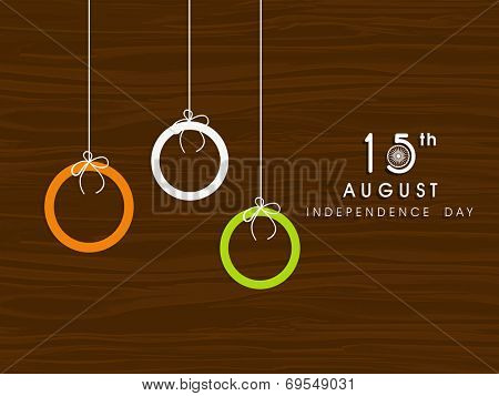 Hanging circles in national tricolors on brown background for 15th of August, Indian Independence Day celebrations.