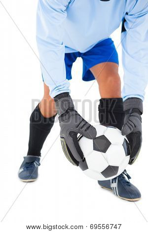 Goalkeeper picking up the ball on white background