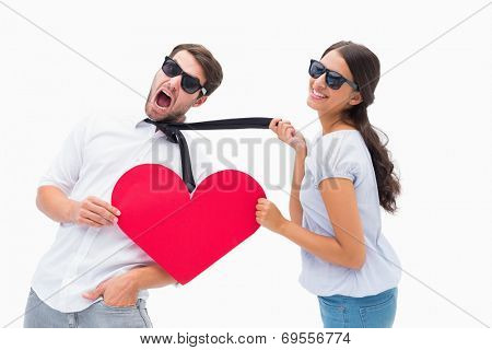 Brunette pulling her boyfriend by the tie holding heart on white background