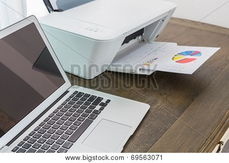 printer and Laptop on wood table
