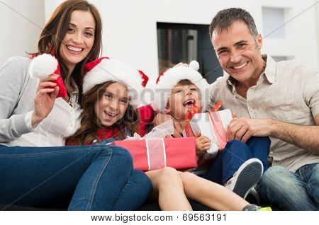 Happy Family Holding Christmas Gift Looking At Camera