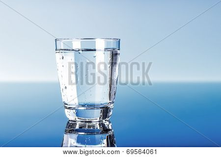 Drinking water in glass on blue