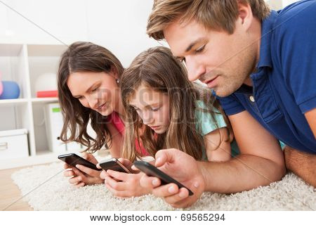 Family Using Smart Phones At Home