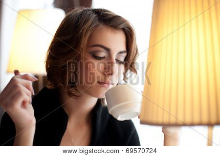 Young beautiful woman in a cafe. Modern trendy blondy girl in the restaurant.