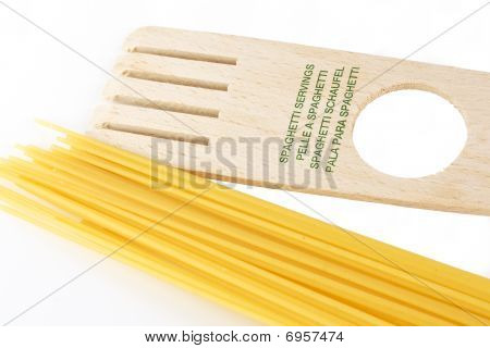 Spaghetti and a tool that measure the servings over white background