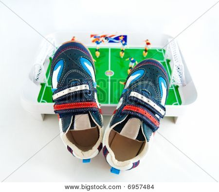 Children's Sports Footwear Against A Toy Football Ground