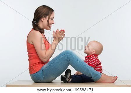 Happy mother and toddler son sitting face to face