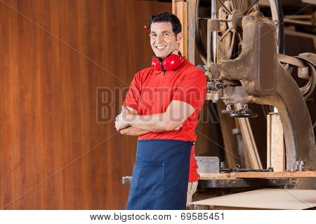 Portrait of confident young carpenter with arms crossed standing in workshop