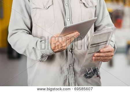 Midsection of male customer checking product through digital tablet in hardware store